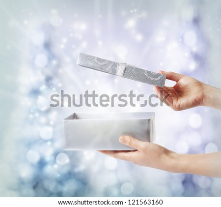 Woman opening a silver gift box on a blue holiday lights background - stock photo
