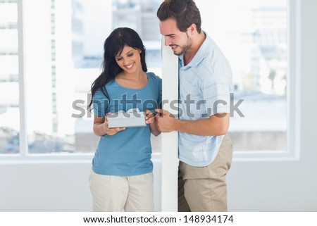 Woman opening boyfriends gift and smiling