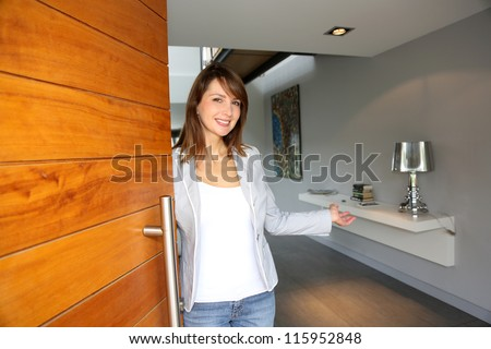Woman opening her house door to welcome people - stock photo