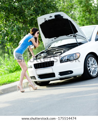 Woman opens car hood and tries to repair the broken car on the road - stock photo