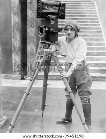 Woman operating movie camera - stock photo