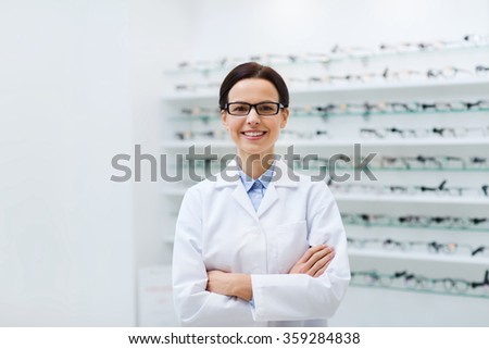 woman optician in glasses and coat at optics store - stock photo