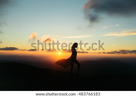 woman or girl silhouette walking at beautiful view on sunset or sunrise in blue sky with clouds and yellow orange sun in mountains on natural background