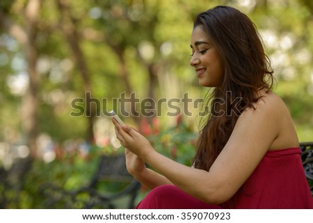 Woman outdoors in park using mobile phone