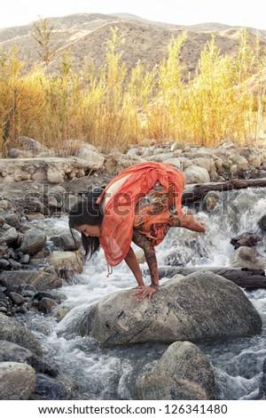 Woman outdoors in yoga pose bakasana in a mountain river. - stock photo