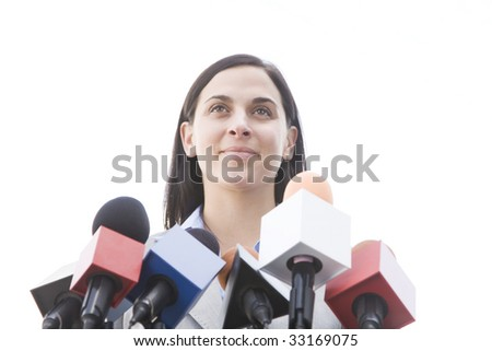 woman outside behind bank of microphones