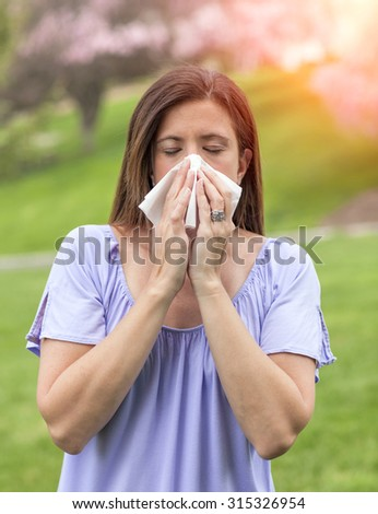 Woman outside blowing nose with a tissue - stock photo