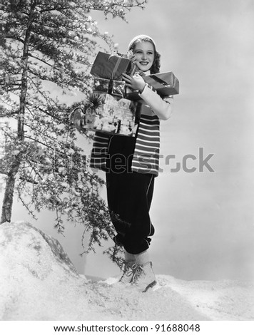 Woman outside in snow with Christmas presents - stock photo