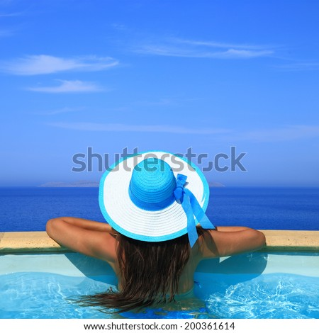 Woman overlooking the sea from swimming pool  - stock photo