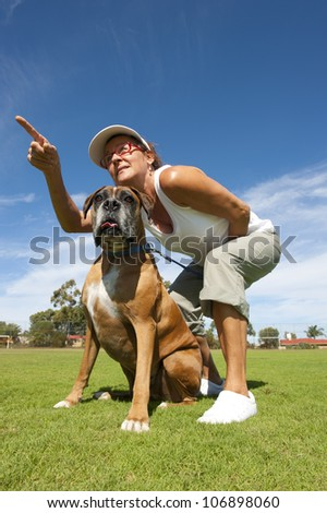 Woman owner with friend and big pet boxer bull dog in park, alert and training, exercising, isolated with blue sky as background and copy space. - stock photo