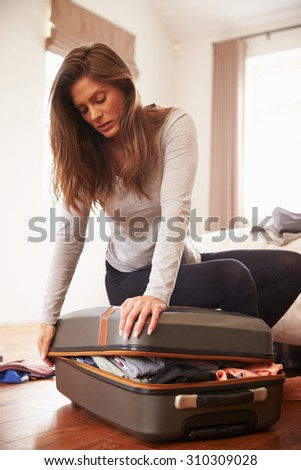 Woman Packing For Vacation Trying To Close Full Suitcase - stock photo