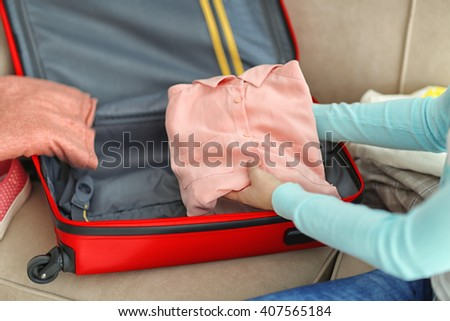 Woman packing her red suitcase, close up - stock photo
