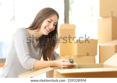 Woman packing or unpacking belongings in a carton box when moving home - stock photo