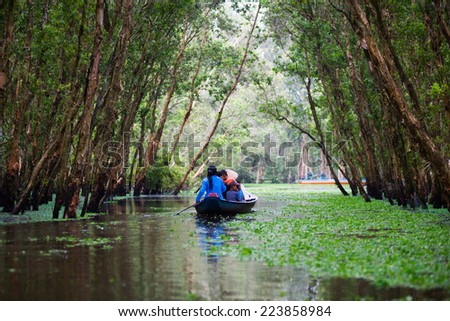 Woman paddling a boat carry tourist in the Tra Su flooded forest, Mekong Delta, An Giang, Vietnam