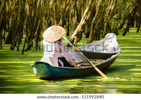 Woman paddling in the  Tra Su flooded forest, Mekong Delta, An Giang, Vietnam - stock photo