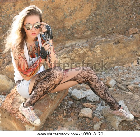 woman painted body art in the form of fire in the t-shirt and denim shorts and torn pantyhose on the background of the industrial buildings of reinforced concrete slabs - stock photo