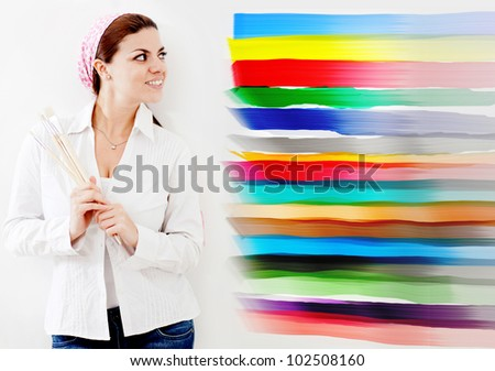 Woman painting a wall of the house and choosing from different colors - stock photo