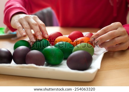 Woman painting Easter egg in one color - stock photo
