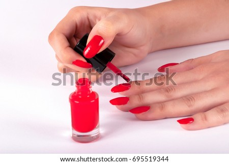 Woman painting her nails on finger in red color on white background
