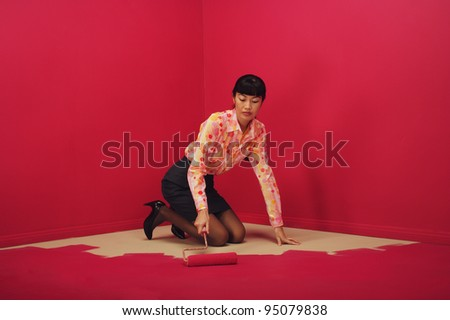 Woman painting herself into a corner - stock photo