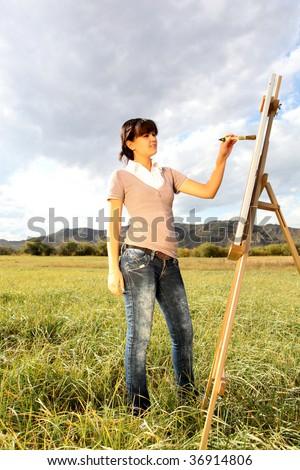 Woman painting landscape - stock photo
