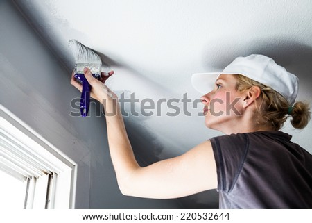 Woman Painting the Edges of the Ceiling with Paintbrush - stock photo