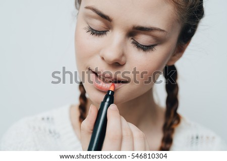 Woman paints her lips with lipstick close up smiling. Lipstick marker