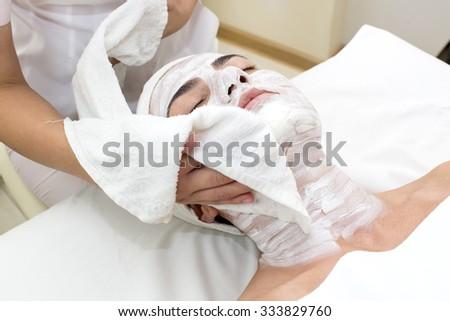 woman passes treatment mask facial at the beauty salon - stock photo