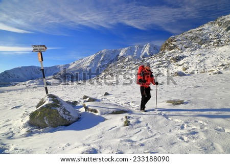Woman passing near trail indicator on snow covered mountain - stock photo