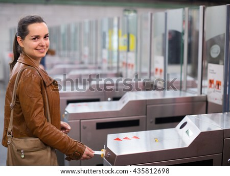 woman passing the turnstile at subway station