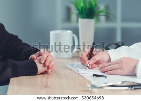 Woman patient applying for medical exam at female doctor's office, general practitioner writing notes in health history record document