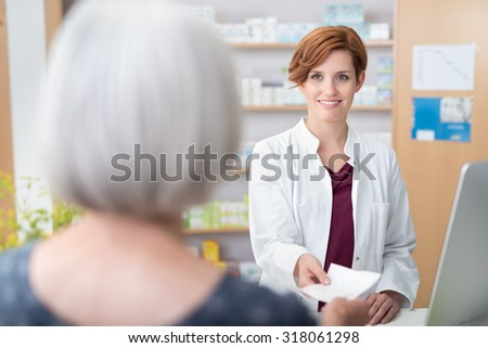 Woman patient handing the pretty young female pharmacist a prescription over the counter, view of the smiling pharmacist over her shoulder - stock photo