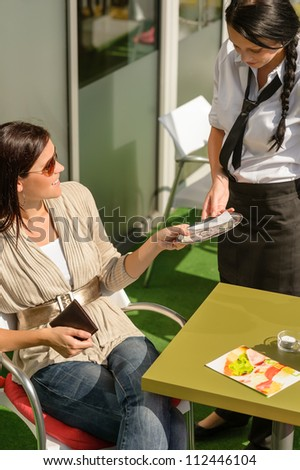 Woman paying bill to waitress cafe restaurant give tip happy - stock photo
