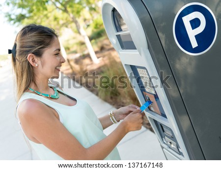Woman paying for parking with a debit card - stock photo
