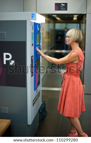 woman paying parking on machine in shopping mall - stock photo