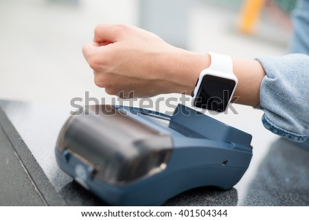 Woman paying the bill by smart watch by NFC technology