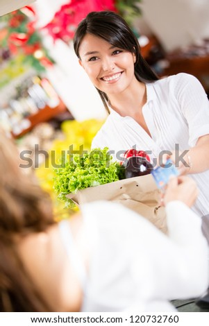 Woman paying with a credit card at the checkout - stock photo