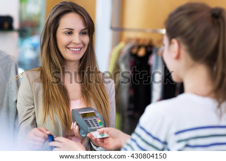 Woman paying with credit card in clothing store  - stock photo