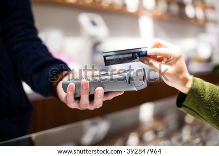 Woman paying with NFC technology on credit card - stock photo