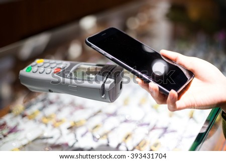 Woman paying with NFC technology on mobile phone - stock photo