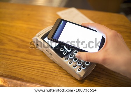 Woman paying with NFC technology on mobile phone, restaurant, shop - stock photo