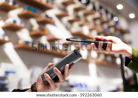 Woman paying with NFC technology on smart phone - stock photo