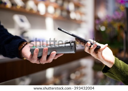 Woman paying with smartphone - stock photo