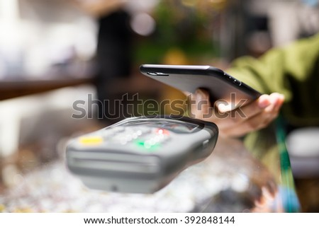 Woman paying with smartphone by NFC - stock photo