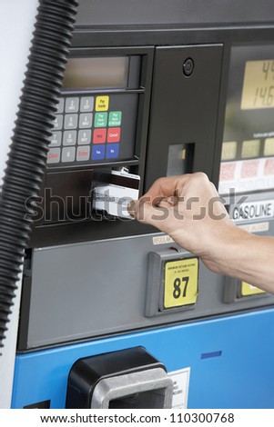 Woman pays for gasoline at the station - stock photo