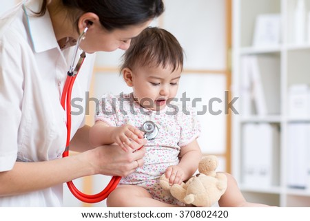 woman pediatrician examining of baby kid with stethoscope - stock photo