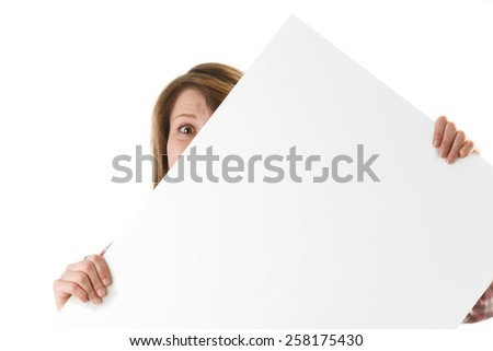 Woman peeking from behind a white sign - stock photo