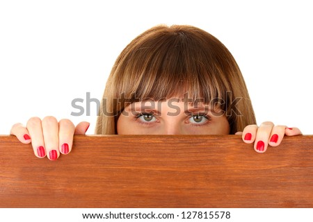 Woman peeking from wooden desk, isolated on white - stock photo
