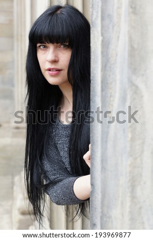 woman peeking out from behind a sandstone pillar