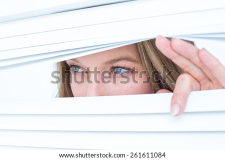 Woman peering through roller blind on white background